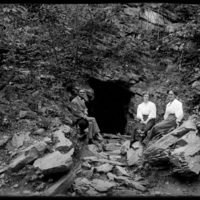 Mabel Wohlbrück and two others sitting at the entrance to a cave