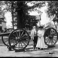 Mabel Wohlbruck and man standing beside a large cannon